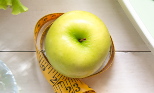Green apple , scale, water bottle, lettuce and measuring tape on a white background.