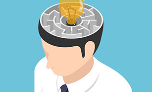 Lightbulb of ideas in the center of maze making up the inside of businessman's head
