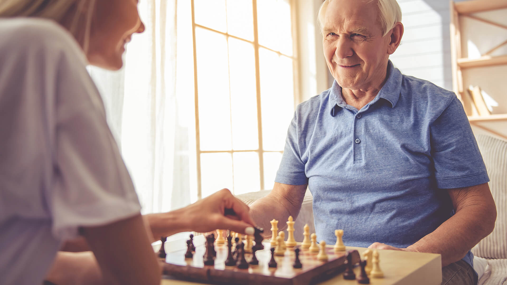 Young woman playing chess with older man