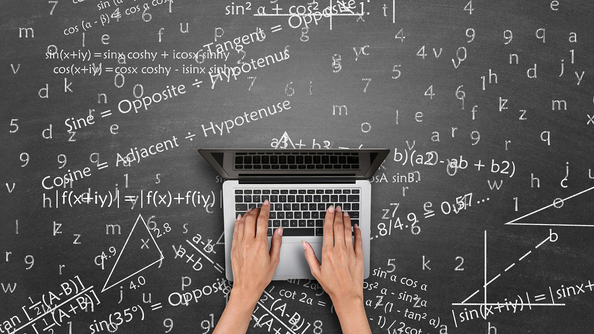Blackboard with trigonometry calculations and laptop on top